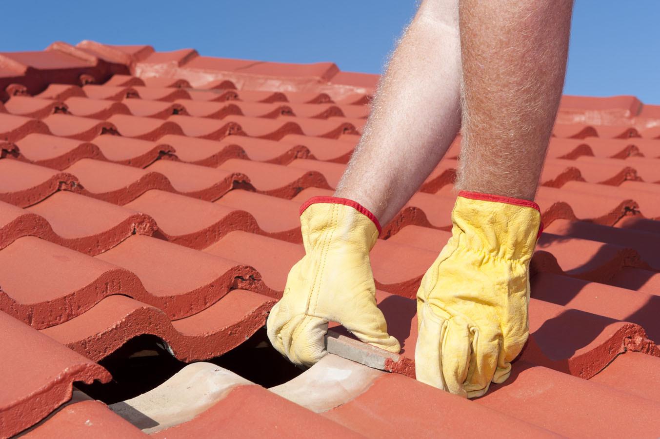 Worker repairing roof tiles on house